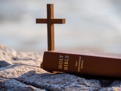 Bible and wood holy cross with blue water as background. Faith in God. Pray for you. Miracle from heaven. Believe in goddess.Love study bible.Holy book, book of life, Christian background concept.