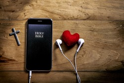 Bible app in smart phone, symbol of christian is love and read and listen to the voice of God, christian concept.