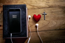 Bible app in smart phones with the Bible on wooden table, read and listen to the voice of God, symbol of christian concept.