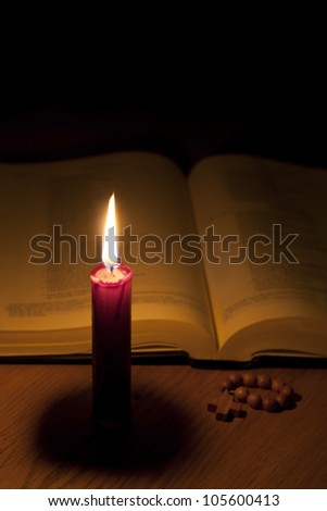 Bible candle and rosary in night background concept