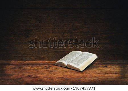 Bible on a old wooden table background.