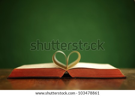 Bible on table with pages folded into heart shape