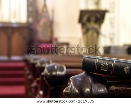 Bible resting on the back of a church pew. Shallow DOF with sharp focus on bible.