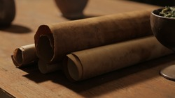 Bible scene: a wooden dining table with scripture scrolls. Close-up of rolls of old paper, cup with food.