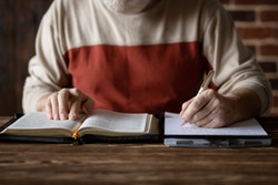 Bible study following the word of Scripture and copying it on paper. Taking notes and study of the Holy Bible. Searching for a spiritual subject