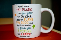 Bible verse Jeremiah 29:11 printed in colorful font on a white ceramic mug isolated on orange table mat. This is a popular verse among Christians.