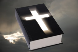 Bible with lighting cross and sky in background