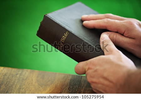 Bible with mans hand resting on the cover whilst holding in front of a green background