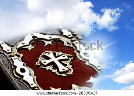 bible with white cross over blue sky with light flare