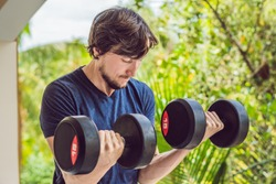 Bicep curl - weight training fitness man outside working out arms lifting dumbbells doing biceps curls. Male sports model exercising outdoors as part of healthy lifestyle