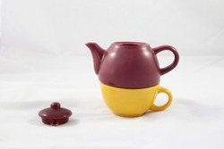Bicolor ceramic teapot on white background. Side view of a maroon and yellow teapot. The upper space is where the tea rests and the yellow part below is the cup. The lid of the teapot is separated.