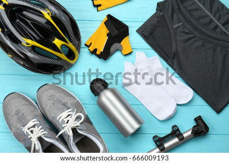 Bicycle accessories and biking clothes on color wooden background #666009193