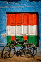 Bicycle and door painted in India national flag colors. Blue city of Jodhpur, Rajasthan, India