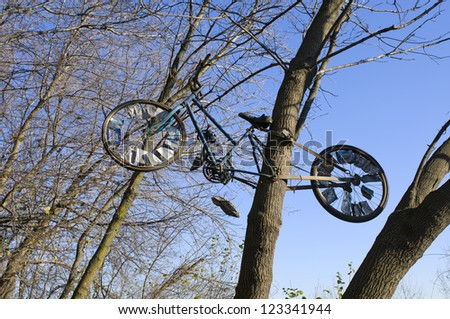 Bicycle attached to tree trunk in woods along urban trail - stock photo