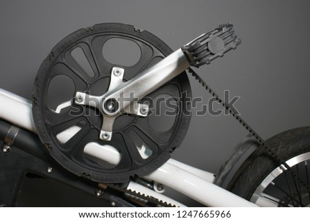 Bicycle crank. Belt driven bicycle crank on a fold up bike. Large plastic crank and cast aluminum arm. Single gear crank on a bicycle