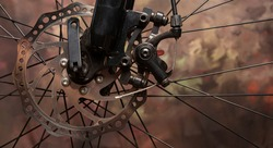 Bicycle details, disc brake and spokes details, dark abstract background, selective focus.