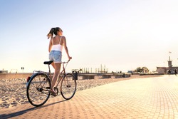 Bicycle fun on beach promenade. Happy woman riding bike on sunny summer boulevard. Seaside waterfront street for cycling. Stylish cyclist lady. Cool carefree feeling at sunset. Summertime freedom.