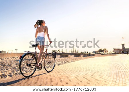 Bicycle fun on beach promenade. Happy woman riding bike on sunny summer boulevard. Seaside waterfront street for cycling. Stylish cyclist lady. Cool carefree feeling at sunset. Summertime freedom. Photo stock ©