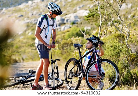 Bicycle has flat tyre and man helps his girlfriend pump it up. outdoors mountain bike couple.
