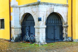 Bicycle in the old town . Ecological type of transport . Bike near black gates