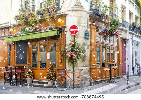 Bicycle is parked at typical Parisian cafes decorated for Christmas holidays in Paris, France