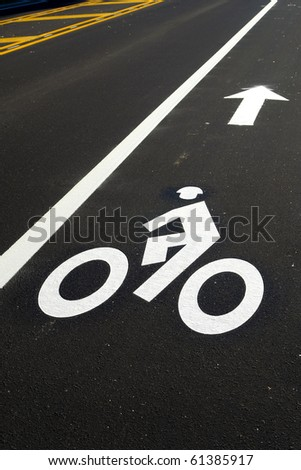 Bicycle lane painted with bike symbol and direction arrow on street pavement of a new road priority bike path