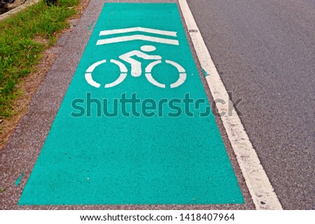 Bicycle lane sign marked on the road in green with painted symbols in white.  #1418407964