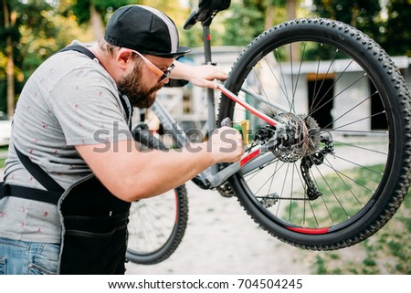 Bicycle mechanic adjusts back disk brakes #704504245