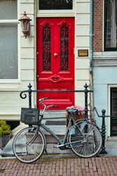 Bicycle near door of old house in Amsterdam street. Bicycles are the very popular means of transport in Netherlands. Amsterdam, Netherlands
