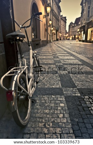 Bicycle on an empty alley with lanterns in Prague at dawn