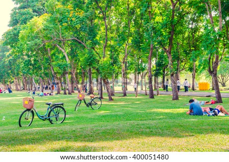 Bicycle on green grass in the park. People relaxing. Happy family enjoy time together outside. togetherness, love, happiness concept. #400051480
