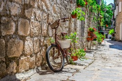 Bicycle on old street with flowers in summer Perast, Montenegro
