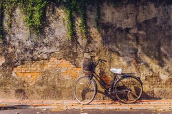 Bicycle on roadside with peeling brick wall background. Bicycle in front of brick wall. Toned image.