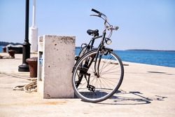 Bicycle on the fishing port of a small seaside town over blue sea and clear blue sky background, spring. Old and vintage bicycle at the railing near the sea.
