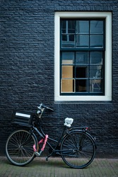 Bicycle parked at house wall in Amsterdam street. Bicycle is a famous very popular means of transport in Netherlands. Amsterdam, Netherlands