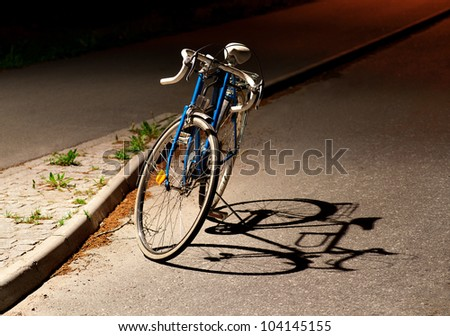 Bicycle parked under a street light at night with shadow