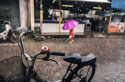 bicycle parking beside alleyway with rain falling and one person walking and holding pink umbrella in a rain in background blur
