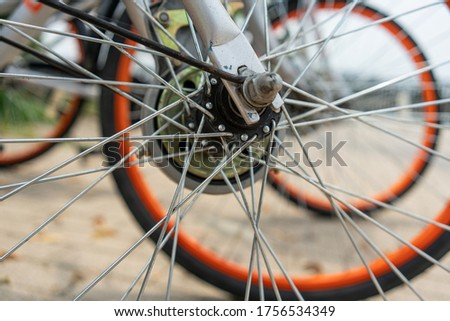 bicycle rent Public bicycles, sharing bikes saddle. Detail view of a bike wheel with more bicycles lined up. Bicycle rent. Closeup of bicycle wheels