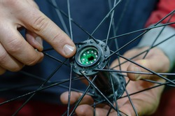 bicycle repair. Changing the lubrication and cleaning the bearings of the bike hubs. New shiny bearings installed in the hub. Texture of the skin close up. Hard-working hands