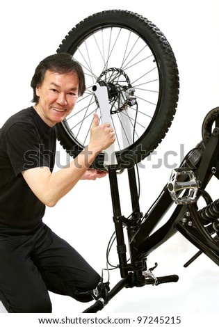 bicycle repair mechanic working on wheel installation in servicing alignment workshop. . white background - stock photo