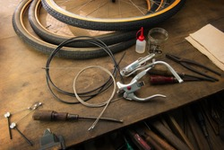 Bicycle repair. Repairing or changing a tire, brakes etc of an vintage bicycle. Old bicycle wheels on a grungy work desk with well used tools and bicycle parts.