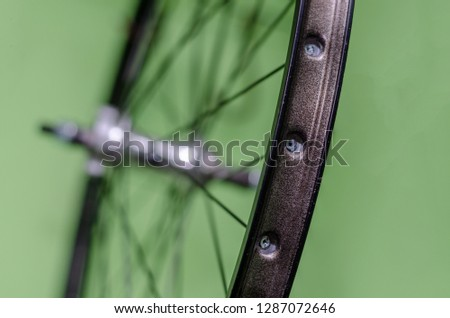 Bicycle repair workshop. On the hook hang new wheels. The hub is black and the spokes and rim are silver. The old bike here is gets a second chance. Parts close-up.   #1287072646
