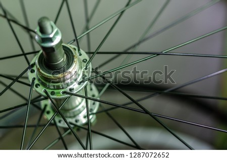 Bicycle repair workshop. On the hook hang new wheels. The hub is black and the spokes and rim are silver. The old bike here is gets a second chance. Parts close-up.   #1287072652
