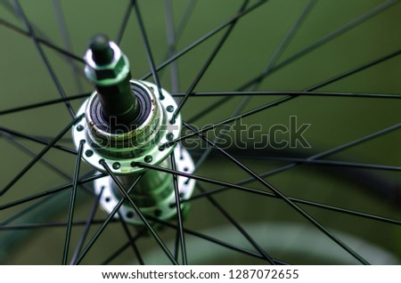 Bicycle repair workshop. On the hook hang new wheels. The hub is black and the spokes and rim are silver. The old bike here is gets a second chance. Parts close-up.   #1287072655