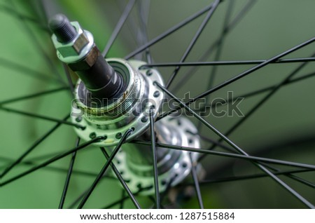 Bicycle repair workshop. On the hook hang new wheels. The hub is black and the spokes and rim are silver. The old bike here is gets a second chance. Parts close-up.   #1287515884