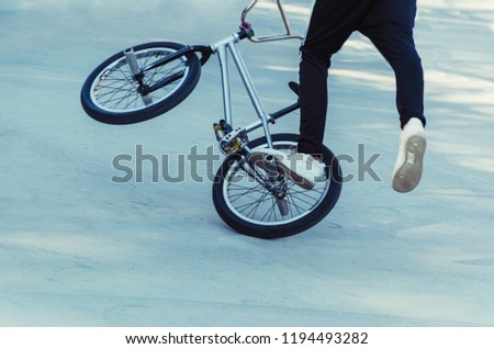 bicycle rider performing a trick on flatland bmx freestyle