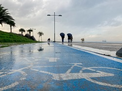Bicycle road in the seaside in Izmir, Turkey. Cloudy and rainy weather and bike road. Blue bicycle road sign, people are walking with umbreallas.