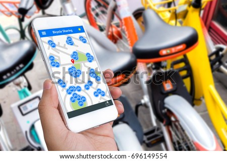 Bicycle sharing service or rental technology concept. Sharing economy and collaborative consumption. Customer hand using mobile phone to find bicycle for ride. Stock photo ©