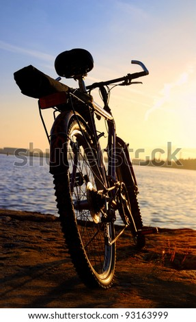 Bicycle silhouette against colorful sunset and industrial port background