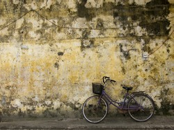Bicycle slightly on a yellow house wall, Hoi An , Vietnam.